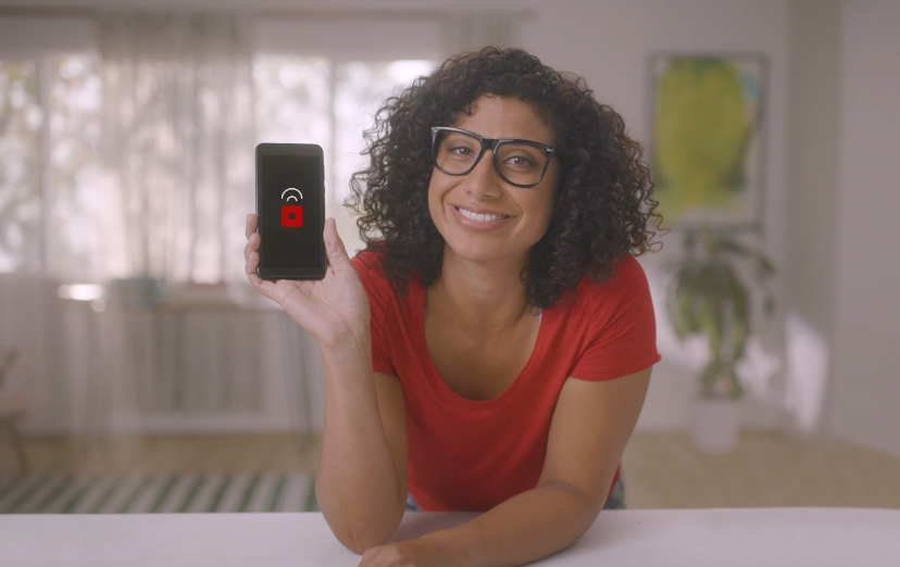 Woman in red shirt and glasses holding a cell phone